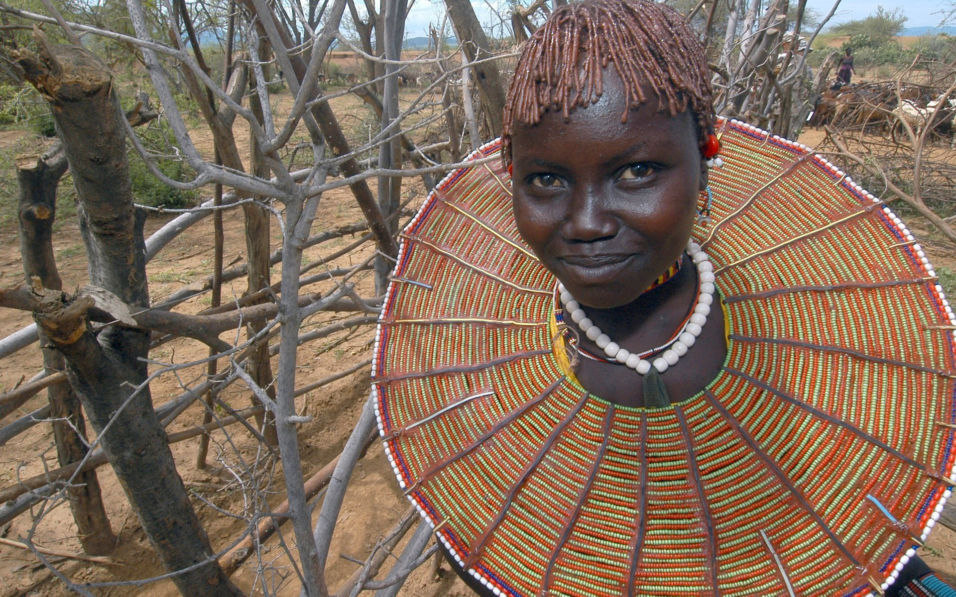 A Pokot girl poses for a photograph. Her necklace signifies that she is engaged to be married. She is not considered an adult yet because she does not wear either the second neckpiece, signifying her marriage, or the traditional black feather on her head, signifying her circumcision. In this part of Kenya, female circumcision is common, and, among the Pokot, is considered a rite of passage into female adulthood.